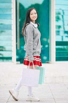 Portrait en pied d'une écolière asiatique positive avec des sacs à provisions