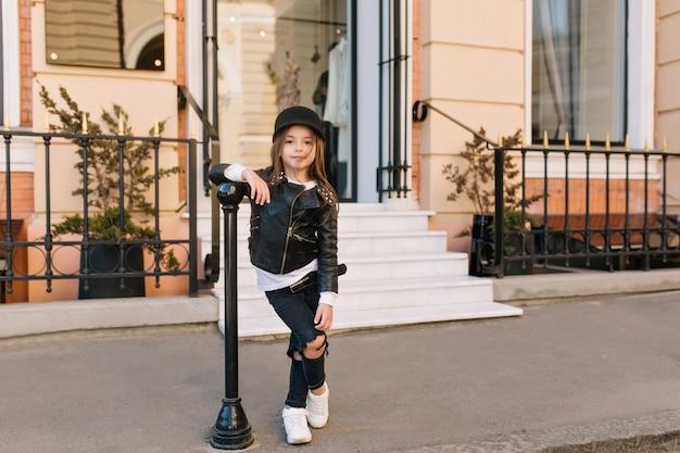 Portrait en pied de l'élégant enfant debout avec les jambes croisées à côté du pilier de fer en face de la boutique.
