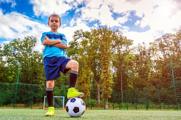 Portrait en pied d'un enfant en tenue de sport posant avec un ballon de football à l'extérieur