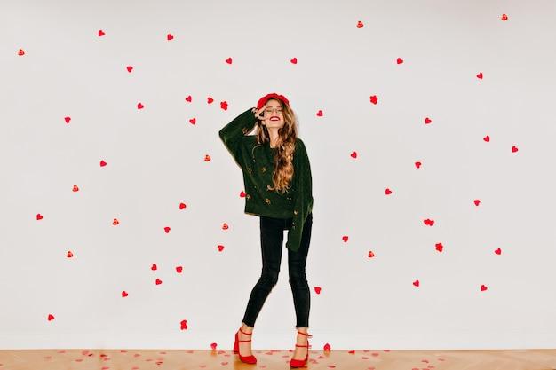 Portrait en pied de femme aux cheveux brun clair debout sous des confettis coeur