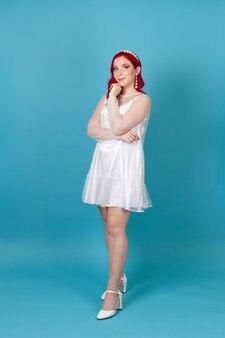 Portrait en pied de femme aux cheveux rouges dans une robe en maille de soie blanche