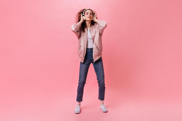 Portrait en pied d'une femme bouclée en jeans dansant tout en écoutant de la musique dans les écouteurs