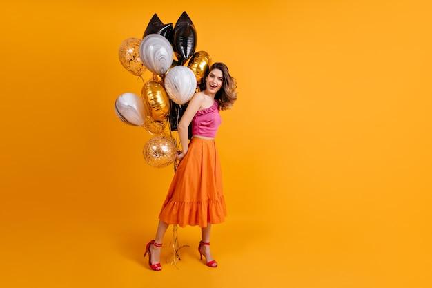 Portrait en pied de femme brune posant à la fête