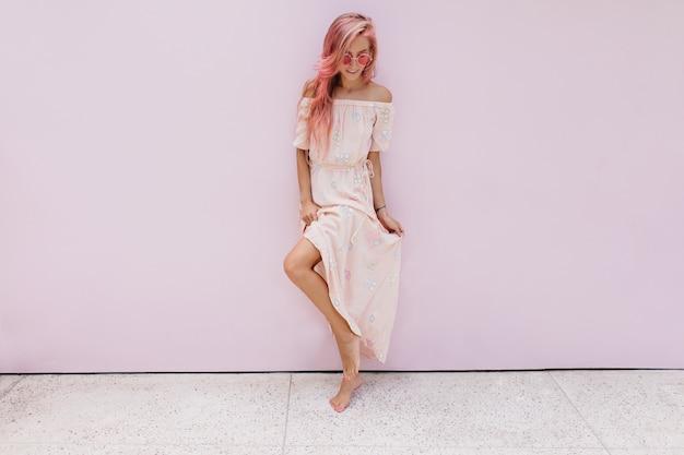 Portrait en pied d'une femme caucasienne rêveuse jouant avec sa robe d'été.