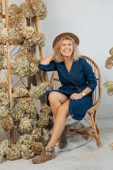 Portrait en pied, de femme décoratrice, près d'un escalier en bois décoré de fleurs d'hortensia séchées. elle est assise sur une chaise en osier, porte un chapeau, une robe en jean et sourit partout. décor naturel
