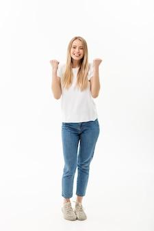 Portrait en pied d'une femme joyeuse en chemise blanche et jean célébrant son succès sur fond blanc.