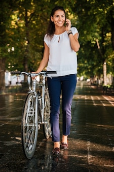 Portrait en pied d'une femme joyeuse heureuse avec phpne mobile et vélo