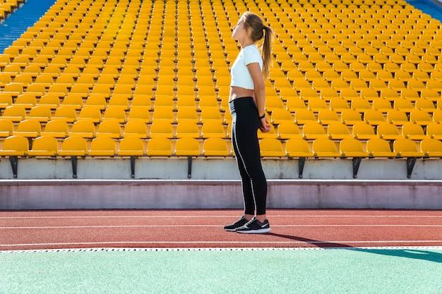 Portrait en pied d'une femme de remise en forme reposant sur le stade