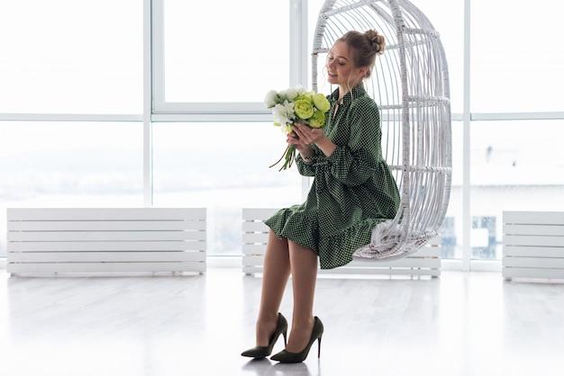 Portrait en pied d'une femme romantique blonde est assis sur la chaise contre la fenêtre, tenant un bouquet de pivoines - image