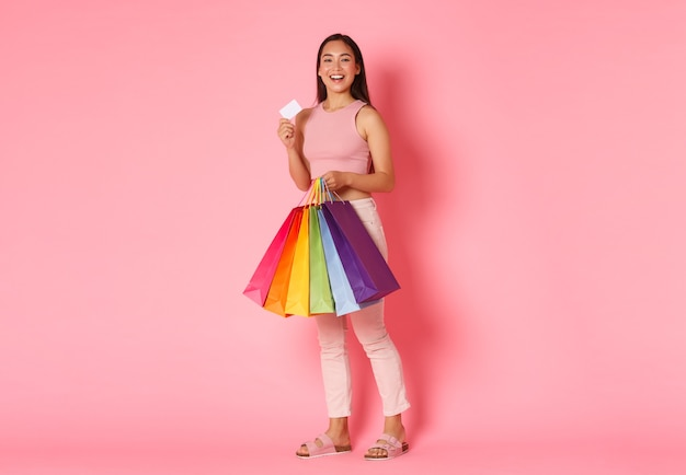 Portrait en pied d'une fille asiatique à la mode optimiste et excitée, souriante, montrant sa carte de crédit et à la recherche de plaisir, porter des sacs à provisions, acheter de nouveaux vêtements pour les vacances, mur rose.