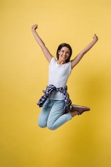 Portrait en pied d'une fille insouciante en chemise blanche et jean, sautant sur fond jaune.