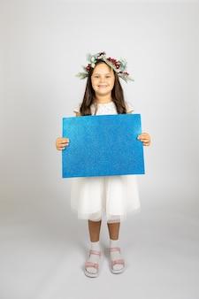 Portrait en pied d'une fille joyeuse qui rit dans une couronne de noël et une robe de fête blanche tenant bl...