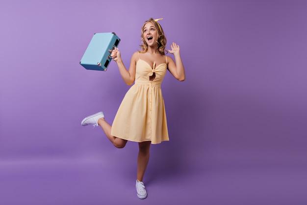 Portrait en pied d'une fille mince heureuse en robe jaune dansant avant le voyage. portrait intérieur de jeune femme blithesome bouclée exprimant le bonheur.