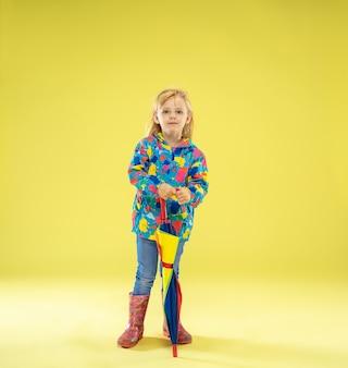 Un portrait en pied d'une fille à la mode lumineuse dans un imperméable tenant un parapluie de couleurs arc-en-ciel sur le mur jaune du studio