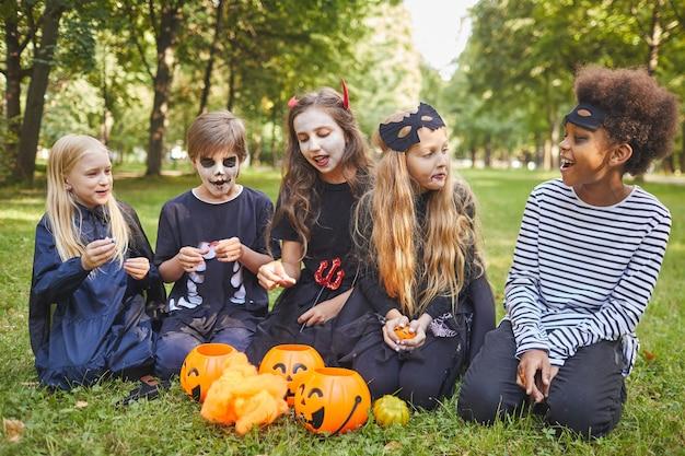 Portrait en pied d'un groupe multiethnique d'enfants mangeant des bonbons à l'halloween à l'extérieur tout en portant des costumes