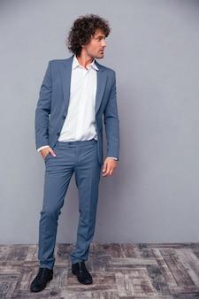 Portrait en pied d'un homme d'affaires attentionné à la recherche de suite sur un mur gris