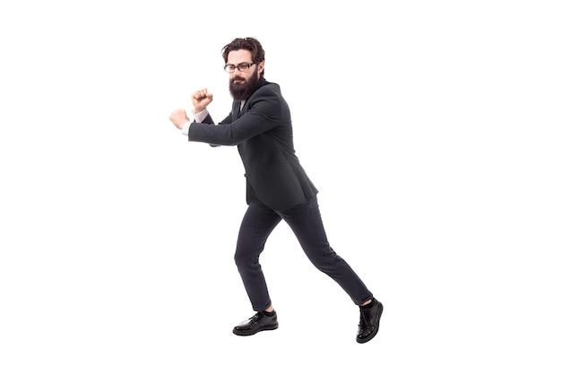 Portrait en pied d'un homme d'affaires barbu tire une corde invisible, isolé sur fond blanc