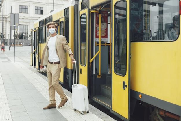 Portrait en pied d'homme d'affaires prospère en masque médical descendant du tramway jaune. bel homme voyageant avec valise blanche