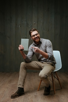 Portrait en pied d'un homme barbu joyeux pointant du doigt la couverture du livre assis sur une chaise isolée sur une surface en bois noire