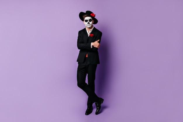 Portrait en pied de l'homme mexicain avec l'art du visage, posant en costume noir classique sur fond isolé.