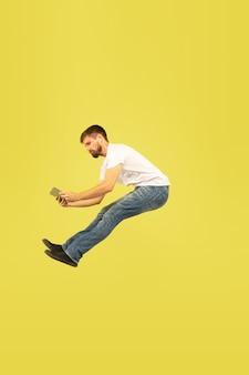 Portrait en pied de l'homme sautant heureux sur fond jaune