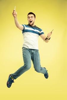 Portrait en pied de l'homme sautant heureux avec des gadgets sur jaune.