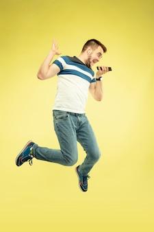 Portrait en pied de l'homme sautant heureux avec des gadgets sur jaune
