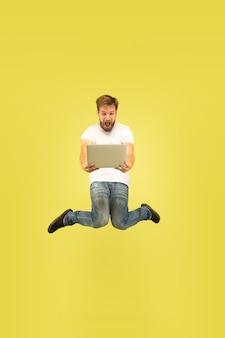 Portrait en pied de l'homme sautant heureux isolé sur jaune