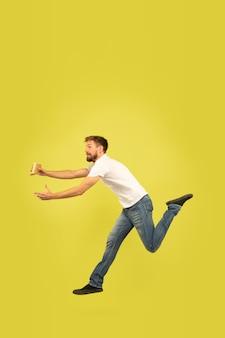 Portrait en pied de l'homme sautant heureux sur mur jaune
