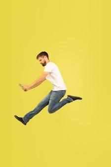 Portrait en pied de l'homme sautant heureux