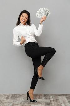 Portrait en pied d'une jeune femme d'affaires heureuse