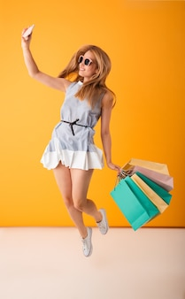 Portrait en pied d'une jeune femme blonde souriante