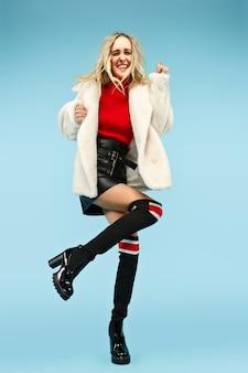 Portrait en pied de jeune femme drôle blonde élégante au studio. concept de mode et shopping féminin.