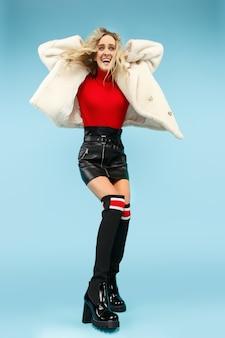 Portrait en pied de jeune femme drôle blonde élégante au studio.