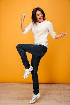 Portrait en pied d'une jeune femme heureuse célébrant