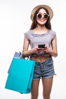 Portrait en pied d'une jeune femme heureuse tenant des sacs à provisions et un téléphone mobile isolé