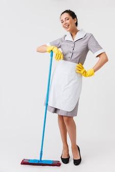 Portrait en pied d'une jeune femme de ménage heureuse