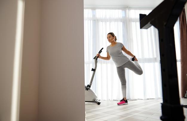 Portrait en pied d'une jeune femme en vêtements de sport gris étirant les muscles des jambes après l'entraînement à la maison en apprenant sa main derrière un vélo d'exercice