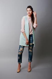 Portrait en pied jeune fille brune vêtue d'une blouse rose, d'une veste turquoise, d'un jean déchiré et de chaussures crème