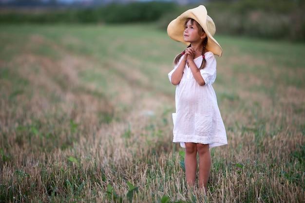 Portrait en pied de la jeune fille mignonne à la mode avec de longues tresses