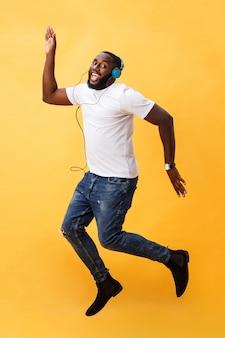 Portrait en pied d'un jeune homme afro-américain cerise, écouter de la musique avec des écouteurs et danser