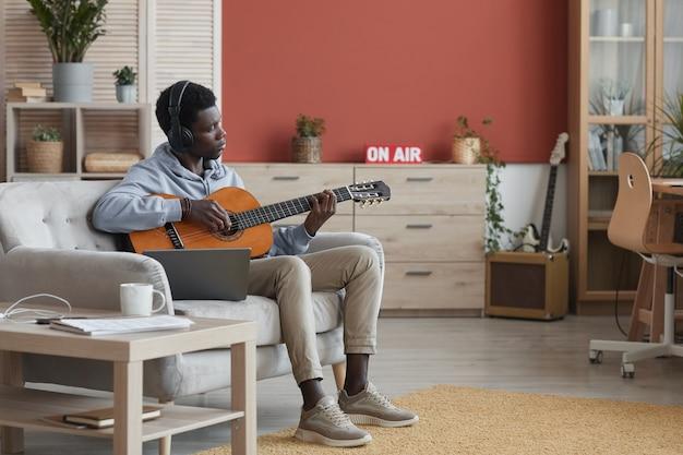 Portrait en pied de jeune homme afro-américain jouant de la guitare acoustique assis sur le canapé et faire de la musique à la maison, copiez l'espace
