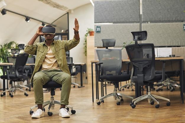 Portrait en pied d'un jeune homme afro-américain portant des vêtements de réalité virtuelle au bureau et profitant de la réalité immersive, copiez l'espace