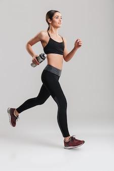 Portrait en pied de jeune instructeur de fitness en survêtement en cours d'exécution tenant une bouteille en métal avec de l'eau douce fraîche à la main, isolé sur mur gris