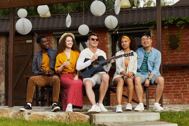Portrait en pied de jeunes bénéficiant d'une fête en plein air en été avec un accent sur l'homme jouant de la guitare et chantant en premier plan