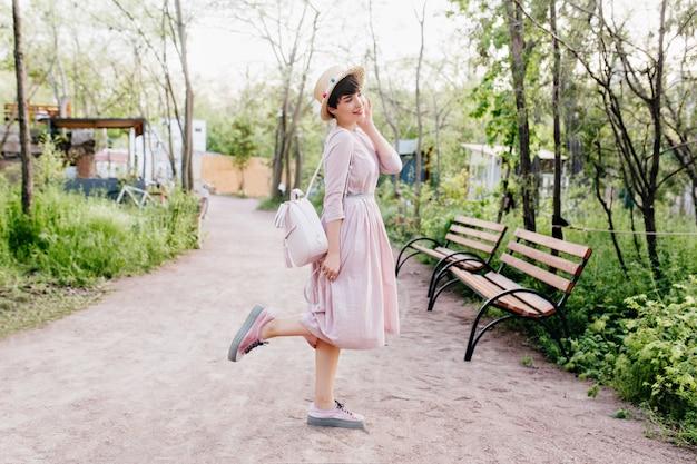 Portrait en pied de jolie dame aux cheveux noirs, posant au milieu de l'allée du parc le matin