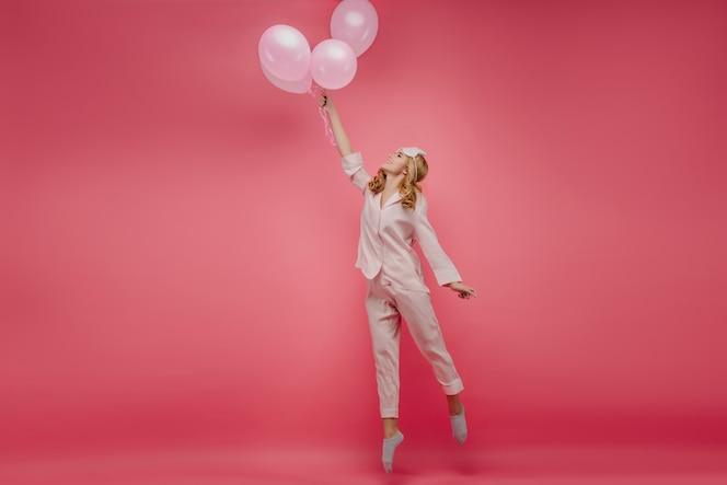 portrait en pied d'une jolie fille insouciante debout sur la pointe des pieds avec des ballons. photo intérieure d'une femme bouclée en vêtements de nuit roses et masque pour les yeux sautant avec le sourire.