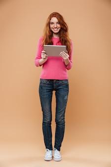 Portrait en pied d'une jolie fille rousse souriante tenant une tablette