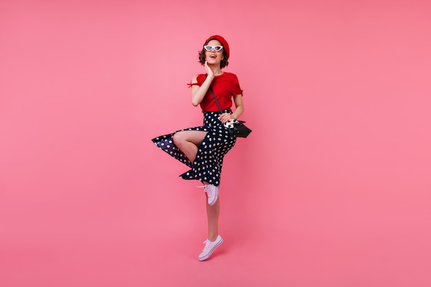 Portrait en pied de joyeuse fille bien habillée s'amusant. debonair dame française aux cheveux bruns courts dansant.
