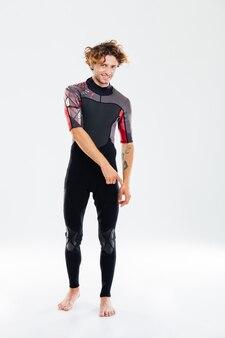 Portrait en pied d'un joyeux sportif bouclé en combinaison de plongée pointant le doigt vers le bas sur un mur blanc